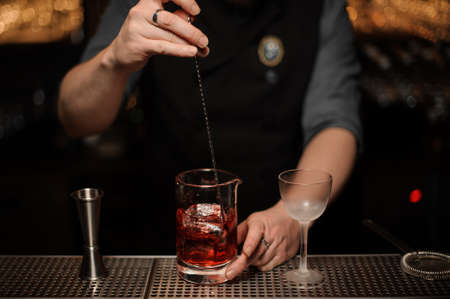Close shot of bartender stirring ice cubes