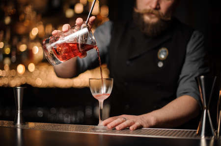 Male bartender pours alcohol cocktail with strainer