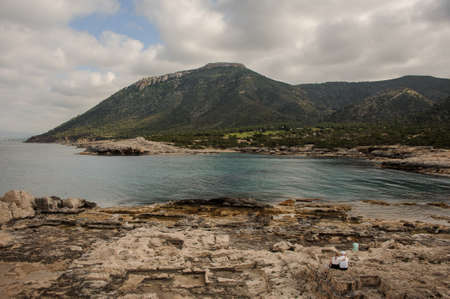 Three people in sportswear on rocky seashore looking at great green mountains in Cyprus Stock Photo