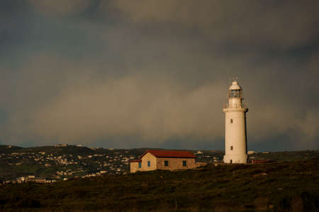 Lighthouse and small building with town in background Imagens