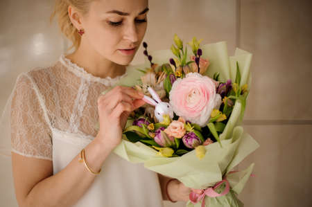 Beautiful girl in white blouse with bouquet