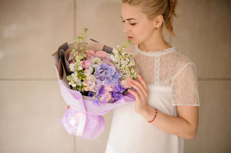 Blond girl with ponytail holds bouquet in purple wrapping Reklamní fotografie - 122903808