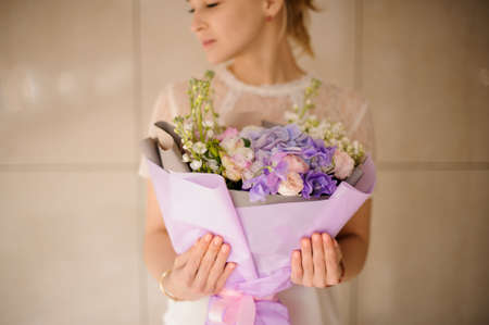 Beautiful girl with ponytail holds bouquet in purple wrapping Reklamní fotografie