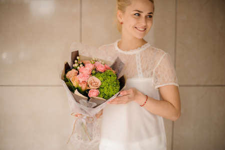 Attractive blond girl holds bouquet in gray wrapping 版權商用圖片