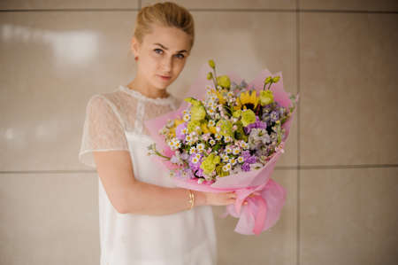 Young girl with astonishing bouquet with daisies Reklamní fotografie - 122903820