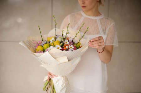 Girl in white dress holding a spring bouquet of tender different color flowers Reklamní fotografie - 122903831