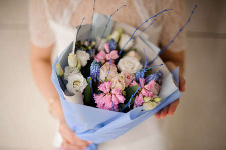 Girl holding a spring bouquet of tender white, pink and blue flowers 스톡 콘텐츠
