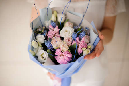 Girl in white dress holding a spring bouquet of tender white, pink and blue flowers 스톡 콘텐츠