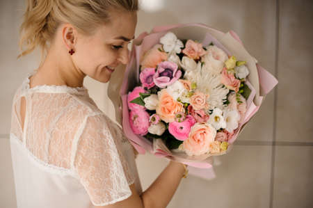Smiling girl holding a spring bouquet of tender white and pink flowers Reklamní fotografie - 122903835