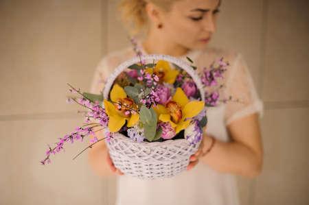 Girl holding a spring white basket of tender yellow orchids Reklamní fotografie - 122903838