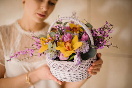 Young girl holding a spring white basket of tender yellow orchids