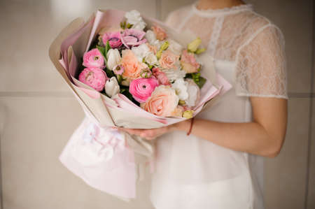 Girl holding a spring bouquet of tender white and pink flowers
