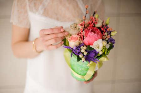 girl holding a spring green pot of tender pink, white and violet flowers Reklamní fotografie