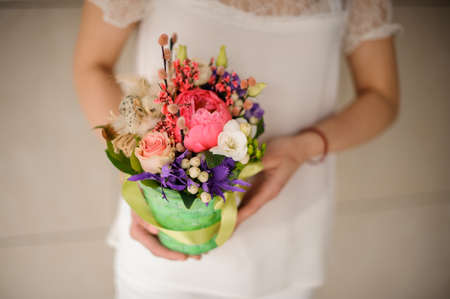 Woman in white dress holding a spring green pot of tender pink, white and violet flowers