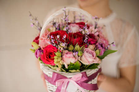Girl holding a spring white basket of red and pink roses