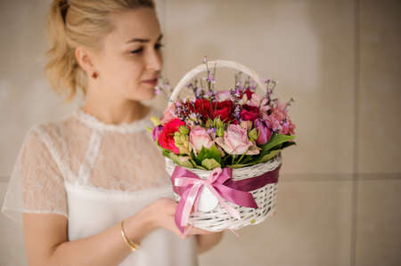 Woman holding a spring white basket of red and pink roses Reklamní fotografie - 122903847