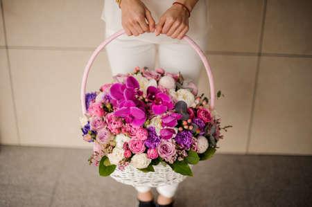 Girl holding a spring basket of tender pink, violet and white flowers Reklamní fotografie - 122904219