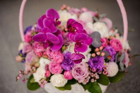 Spring basket of tender pink, violet and white flowers 스톡 콘텐츠