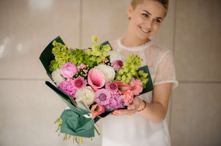 Young blond girl holding bouquet with various flowers Standard-Bild