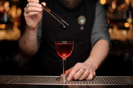 Camarero agregando una baya roja con pinzas al cóctel