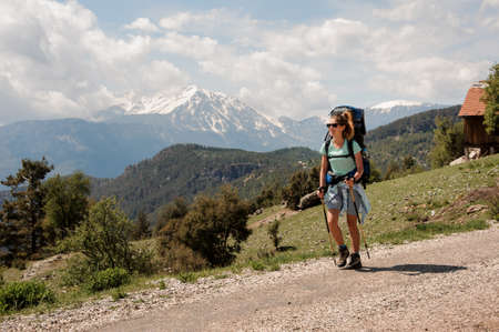 Female backpacker goes down the road in hills Stock Photo