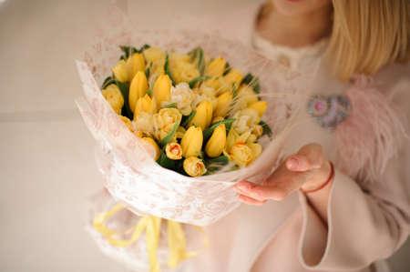 Bunch of yellow tulips in girls hands