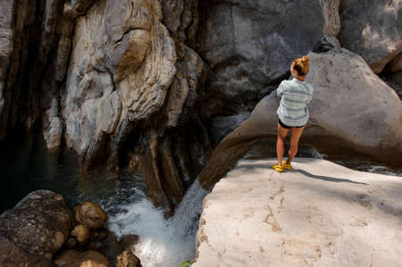 Girl with ponytail watching at waterfall in canyon Reklamní fotografie