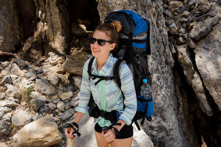 Portrait of female hiker in sunglasses with backpack