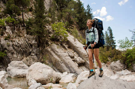 Female hiker stands on stones in canyon