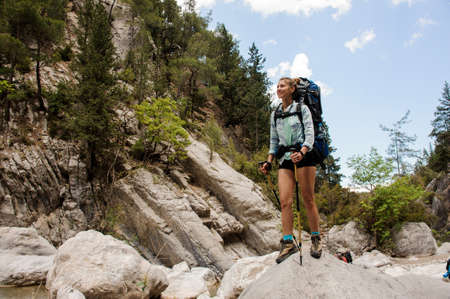 Female hiker travels standing on stones in canyon