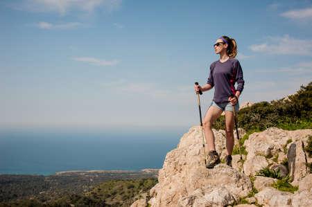 Jolie fille debout sur le rocher en short avec des bâtons de marche