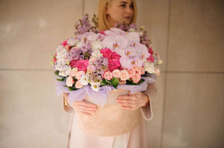 Girl holding a huge spring box of tender multicolored pink flowers Banque d'images