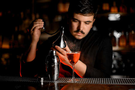 Professional male bartender spraying from the diffuser on the cocktail in the glass