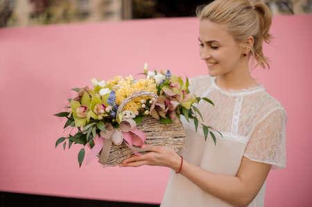 Glückliches Mädchen mit Blumenstrauß im Blumenkorb Standard-Bild