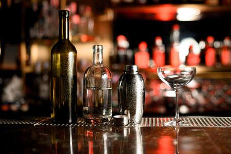 Deux bouteilles, shaker et verre sur comptoir bar Banque d'images
