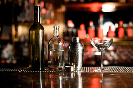 Two bottles, shaker and glass on bar counter Фото со стока
