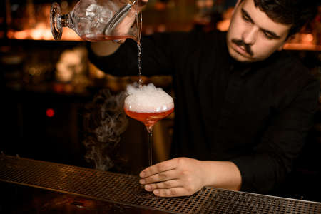 Bartender using strainer to prepare an alcohol cocktail