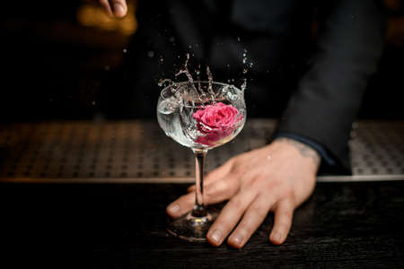 Bartender dropping flower in an alcohol cocktail