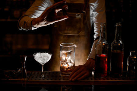 Bartender pouring an essence from the little glass bottle Archivio Fotografico