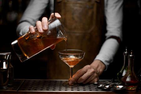Barman masculin versant un cocktail alcoolisé brun de la tasse à mesurer au verre