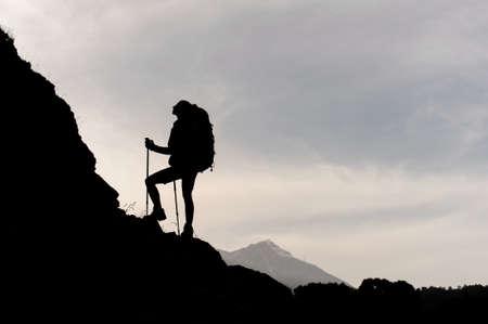 Silhouette des weiblichen Wanderers, der auf den Berg klettert Standard-Bild