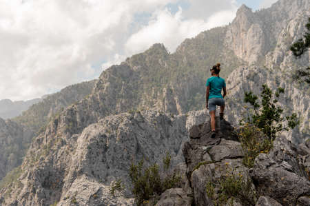 Young girl standing on top of the mountain