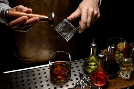 Male bartender making a stamp imprint on the big ice cube