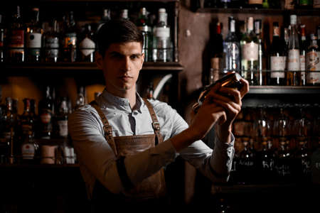 Professional male bartender holding in hands a steel shaker Archivio Fotografico