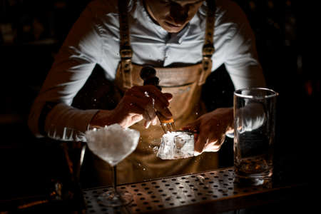 Professional male bartender in leather apron making a crushed with a special instrument