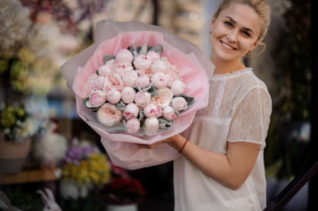 Girl holding a bouquet of tender rose color peonies 免版税图像