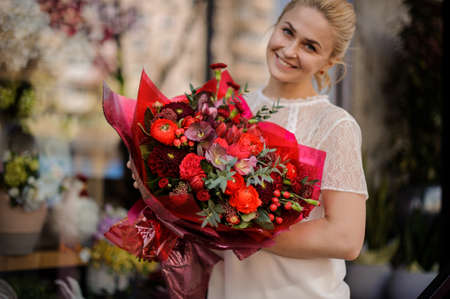Smiling girl holding a bouquet of crimson red flowers 免版税图像