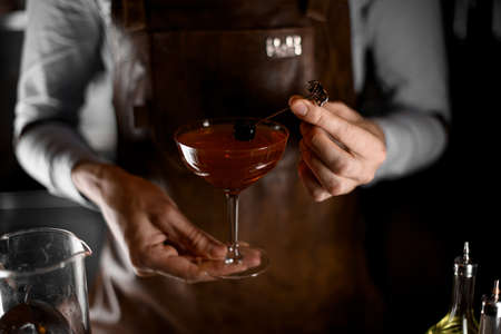 Close-up of bartender holding drink with olive