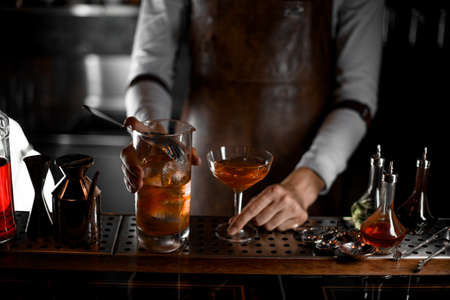 Bartender pouring alcohol cocktail with the strainer Фото со стока