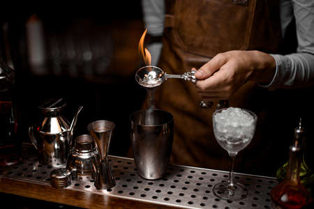 Bartender fires up alcohol in bar spoon